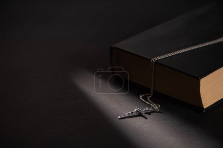 Photo pour Sainte bible avec croix sur fond noir foncé avec des bougies allumées - image libre de droit