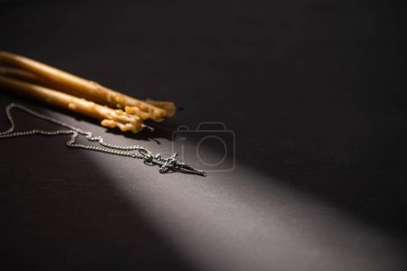 Photo for Cross and church candles on black dark background with sunlight - Royalty Free Image
