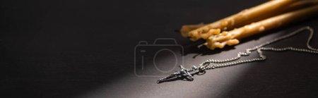 Photo pour Bougies croix et église sur fond noir foncé avec lumière du soleil, vue panoramique - image libre de droit