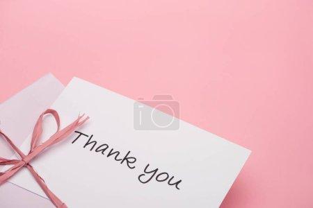 Photo pour Arc rose près de carte de voeux de remerciement sur fond rose - image libre de droit
