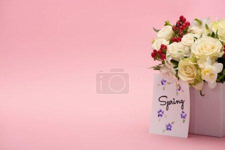 Photo pour Bouquet de fleurs dans une boîte cadeau festive avec carte de voeux de printemps sur fond rose - image libre de droit