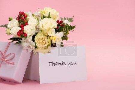 Foto de Bouquet of flowers in festive gift box with bow near thank you card on pink background - Imagen libre de derechos