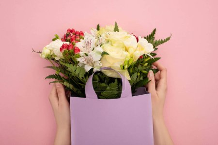 Photo for Cropped view of woman holding bouquet of flowers in violet paper bag on pink background - Royalty Free Image