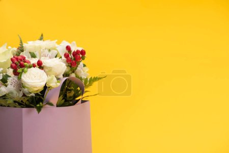 spring fresh bouquet of flowers in violet paper bag isolated on yellow