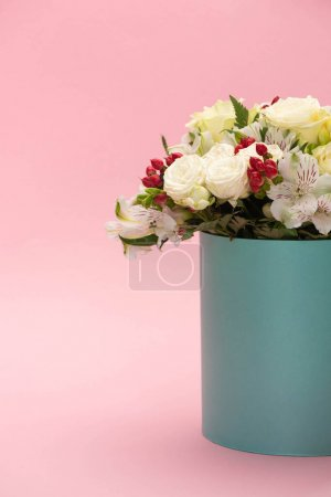 bouquet of flowers in turquoise gift box on pink background