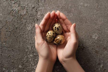 Foto de Partial view of woman holding quail eggs on grey concrete background - Imagen libre de derechos