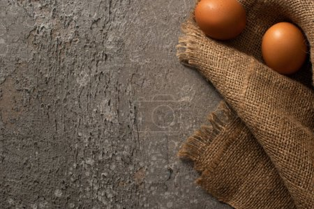 Foto de Top view of brown chicken eggs on sackcloth on grey concrete background - Imagen libre de derechos