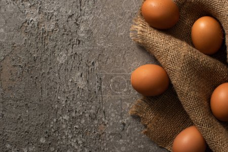 Photo for Top view of brown eggs on sackcloth on grey textured background - Royalty Free Image