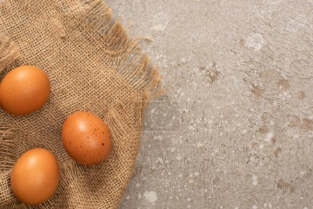 top view of brown chicken eggs on sackcloth on grey cement background