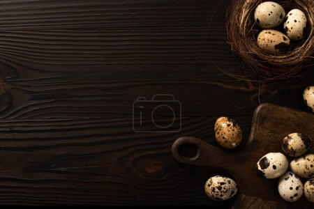 Photo for Top view of quail eggs in brown nest and on chopping board on dark wooden background - Royalty Free Image