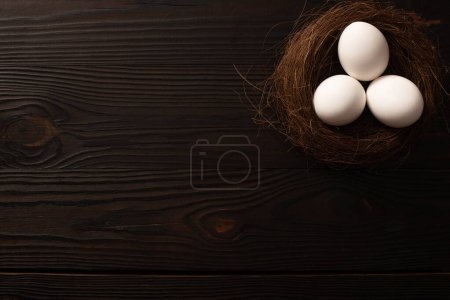 Photo for Top view of white chicken eggs in brown nest on dark wooden background - Royalty Free Image