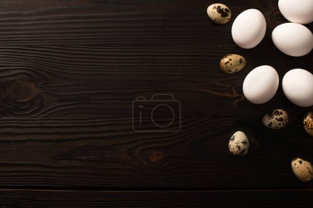 Photo for Top view of white chicken eggs and quail eggs on dark wooden background - Royalty Free Image