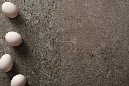 Foto de Top view of white chicken eggs on grey concrete background - Imagen libre de derechos