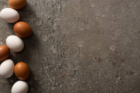 Photo for Top view of brown and white chicken eggs on grey textured background - Royalty Free Image