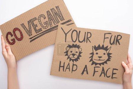 Photo pour Vue partielle de la femme tenant des panneaux en carton avec go vegan et votre fourrure avait des inscriptions faciales sur fond blanc - image libre de droit