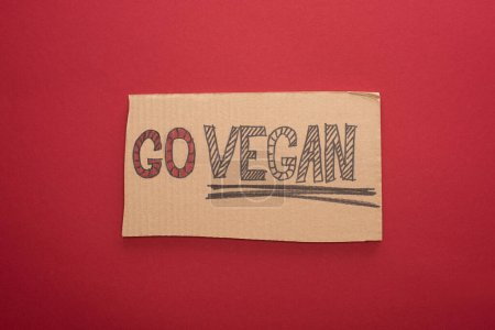 Photo pour Vue du haut du panneau en carton avec inscription go vegan sur fond rouge - image libre de droit