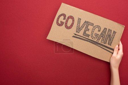 Photo pour Vue partielle de la femme tenant signe avec go inscription végétalienne sur fond rouge - image libre de droit