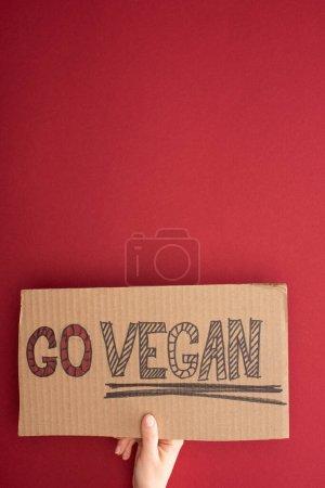 Photo pour Vue partielle de la femme tenant du carton avec inscription go vegan sur fond rouge - image libre de droit