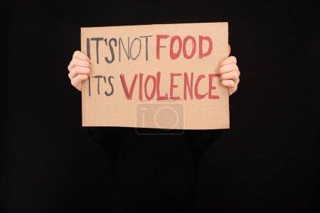 Photo pour Vue partielle d'une femme tenant une pancarte en carton avec son pas de nourriture son inscription violence isolée sur noir - image libre de droit