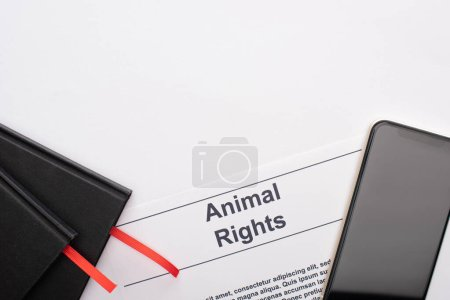 top view of animal rights inscription, black notebooks and smartphone on white background