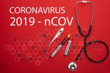 Photo pour Vue du haut du stéthoscope, du thermomètre et des éprouvettes avec échantillons de sang et lettrage du coronavirus 2019-ncov sur fond rouge - image libre de droit