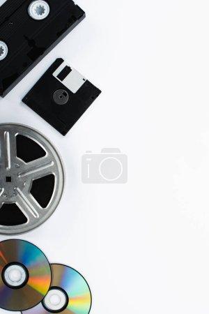 Photo pour Vue de dessus de la cassette VHS, des disques CD, de la disquette et de la bobine de film sur fond blanc - image libre de droit