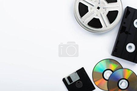 Top view of CD discs, black VHS cassette, diskette...