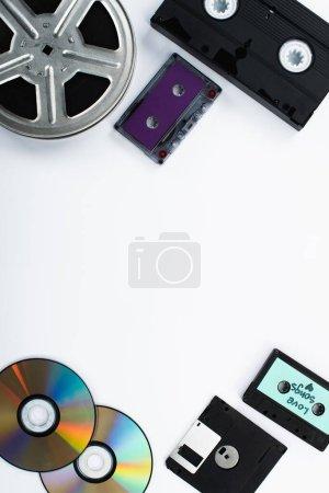 Photo pour Vue de dessus des disques CD, cassettes, cassette VHS, disquette et bobine de film sur fond blanc - image libre de droit