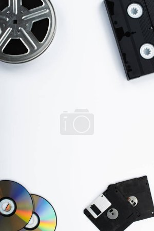 Photo pour Vue de dessus des disques CD, cassette VHS, disquettes et bobine de film sur fond blanc - image libre de droit