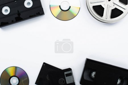 Photo pour Vue de dessus des disques CD, cassettes VHS, bobine de film et disquettes sur fond blanc - image libre de droit