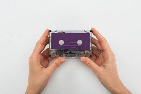 Foto de Vista parcial del hombre que sostiene cassette púrpura sobre fondo blanco - Imagen libre de derechos