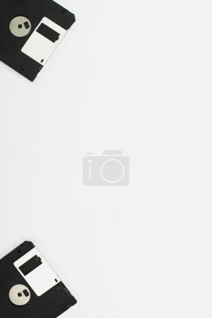 top view of two black diskettes on white background