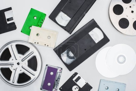 flat lay of VHS cassettes, diskettes, CD discs, film reels and colorful cassettes on white background