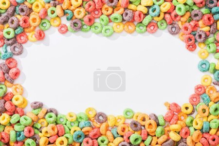 Photo for Top view of bright multicolored breakfast cereal arranged in frame on white background - Royalty Free Image