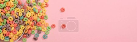 Photo for Top view of bright colorful breakfast cereal scattered from bowl on pink background, panoramic shot - Royalty Free Image