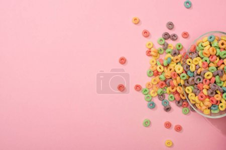 top view of bright colorful breakfast cereal scattered from bowl on pink background