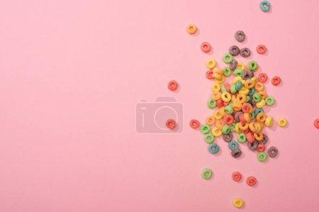 Foto de Vista superior de los brillantes cereales de desayuno multicolor sobre fondo rosa. - Imagen libre de derechos