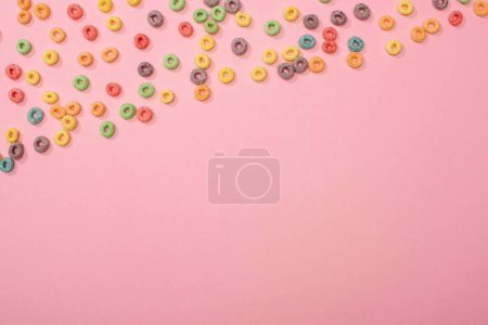 top view of bright colorful breakfast cereal scattered on pink background