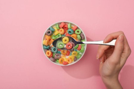 Photo for Partial view of woman eating bright colorful breakfast cereal from bowl with spoon on pink background - Royalty Free Image