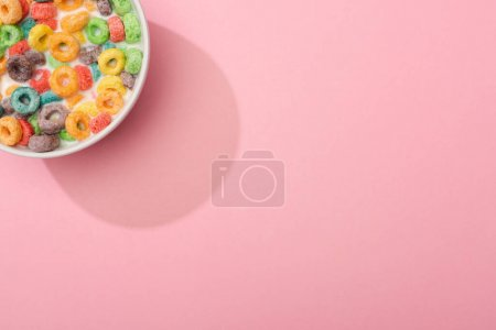Photo for Top view of bright colorful breakfast cereal with milk in bowl on pink background - Royalty Free Image