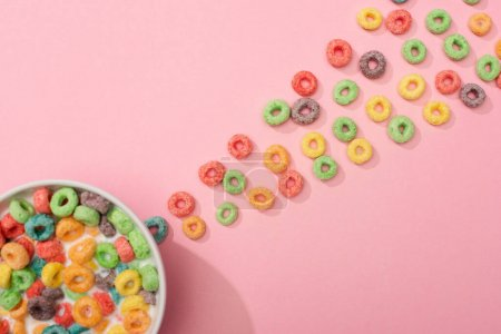 Photo for Top view of bright colorful breakfast cereal with milk in bowl and around on pink background - Royalty Free Image