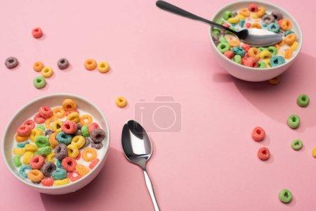 selektiver Fokus von hellen bunten Frühstückszerealien mit Milch in Schüsseln mit Löffeln auf rosa Hintergrund