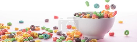 Photo for Bright multicolored breakfast cereal scattered around bowl on white background, panoramic shot - Royalty Free Image