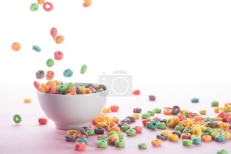 Photo for Bright multicolored breakfast cereal falling in bowl on white background - Royalty Free Image