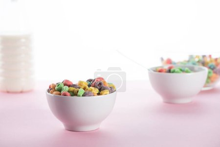 Photo for Selective focus of bright multicolored breakfast cereal in bowls near milk on white background - Royalty Free Image