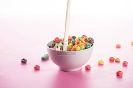Photo for Bright multicolored breakfast cereal in bowl with pouring milk on pink background - Royalty Free Image