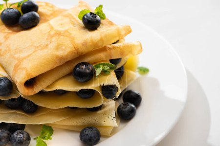 Photo for Close up view of tasty crepes with mint and blueberries on plate on white background - Royalty Free Image