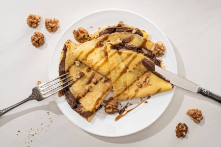 Photo for Top view of tasty crepes with chocolate spread and walnuts on plate with cutlery on grey background - Royalty Free Image