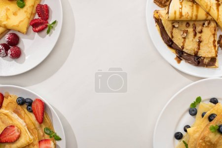 Photo for Top view of tasty crepes with chocolate spread, walnuts and berries on plates on grey background - Royalty Free Image