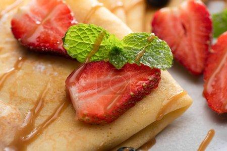 Photo pour Vue rapprochée de crêpes savoureuses aux fraises et menthe - image libre de droit